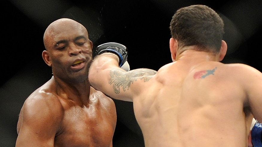 Chris Weidman connects with Anderson Silva during their UFC 162 mixed martial arts middleweight championship bout at the MGM Grand Garden Arena on Saturday, July 6, 2013, in Las Vegas. Weidman won the fight with a TKO. (AP Photo/David Becker)