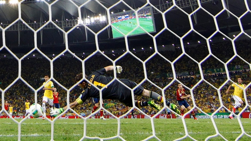 Brazil's Neymar, left, scores his side's 3rd goal past Spain's Iker Casillas during the soccer Confederations Cup final between Brazil and Spain at the Maracana stadium in Rio de Janeiro, Brazil, Sunday, June 30, 2013. (AP Photo/Natacha Pisarenko)