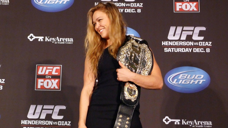 FILE - In this Dec. 6, 2012, file photo, mixed martial arts fighter Ronda Rousey shows off her UFC bantamweight championship belt presented to her by UFC president Dana White during a news conference in Seattle. With her Olympic pedigree and merciless mixed martial arts success, Rousey finally has a showcase worthy of her talent. Rousey and Liz Carmouche are about to make history in the main event at UFC 157 in Anaheim on Saturday, in the first women's bout in the promotion's history.  (AP Photo/The  Canadian Press, Neil Davidson, File)