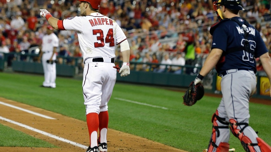 Washington Nationals' Bryce Harper (34) points at Atlanta Braves starting pitcher Julio Teheran as he takes first base after being hit by a pitch during the fifth inning of a baseball game at Nationals Park on Tuesday, Aug. 6, 2013, in Washington. (AP Photo/Alex Brandon)