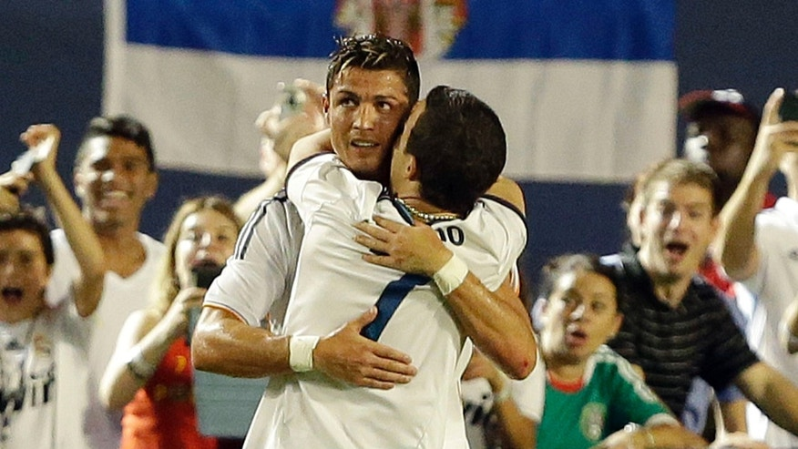 A man who ran onto the pitch hugs Real Madrid forward Cristiano Ronaldo, rear, during the second half of the International Champions Cup final soccer game between Real Madrid and Chelsea, Wednesday, Aug. 7, 2013, in Miami Gardens, Fla. (AP Photo/Wilfredo Lee)