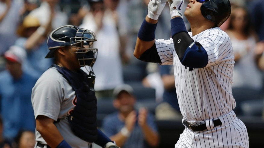 New York Yankees' Alex Rodriguez, right, gestures after hitting a second-inning solo home run in a baseball game against the Detroit Tigers, Sunday, Aug. 11, 2013, in New York. (AP Photo/Kathy Willens)