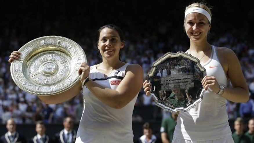 July 6, 2013: Marion Bartoli of France, left, holds her winners trophy as she stands alongside Sabine Lisicki of Germany during the trophy ceremony after the Women's singles final match at the All England Lawn Tennis Championships in Wimbledon, London. (AP)