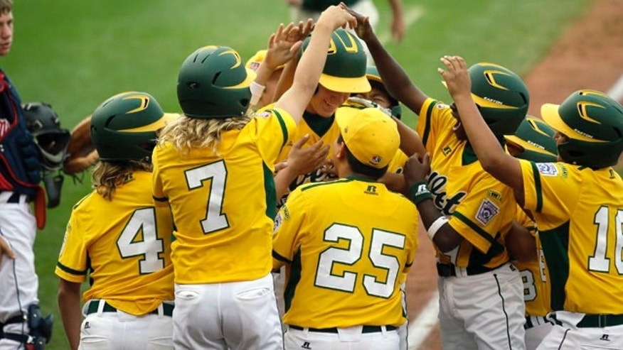 Aug. 19, 2013: Chula Vista, Calif. players surround Grant Holman, center, after his game-winning grand slam off Newark, Del.'s David Hawtof during the fourth inning of a baseball game in United States pool play at the Little League World Series tournament.