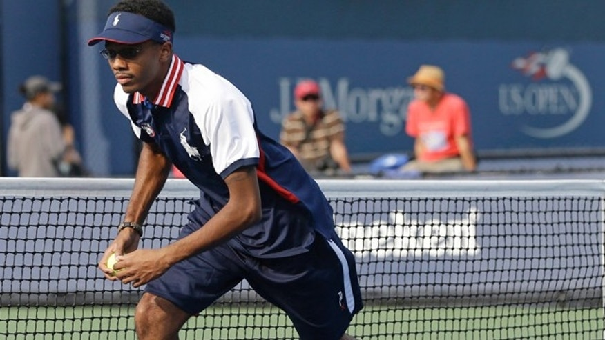 Aug. 21, 2013: Angelo Anderson works during a tennis match as a ballperson at the Billie Jean King National Tennis Center in New York.