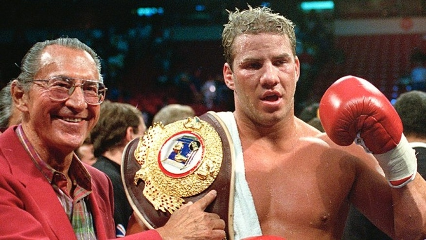 June 7, 1993: Newly crowned WBO heavyweight champion Tommy Morrison receives his championship belt after defeating George Foreman in Las Vegas, Nev. Morrison, a former heavyweight champion who gained fame for his role in the movie 'Rocky V' has died. He was 44. Morrison's former manager, Tony Holden says his longtime friend died Sunday night at a Nebraska hospital.  (AP/Nick Ut, File)