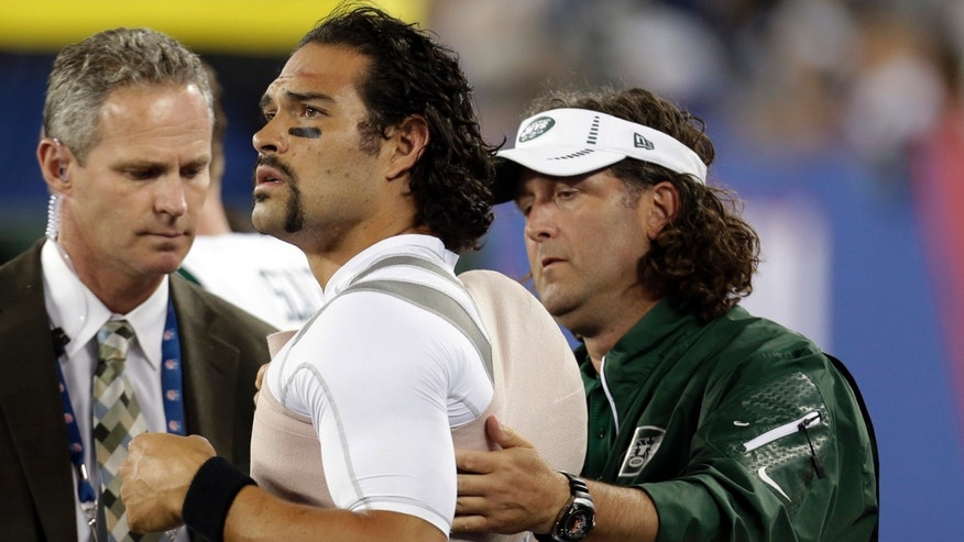 A trainer wraps New York Jets quarterback Mark Sanchez, center, during the second half of a preseason NFL football game against the New York Giants, Saturday, Aug. 24, 2013, in East Rutherford, N.J. (AP Photo/Julio Cortez)