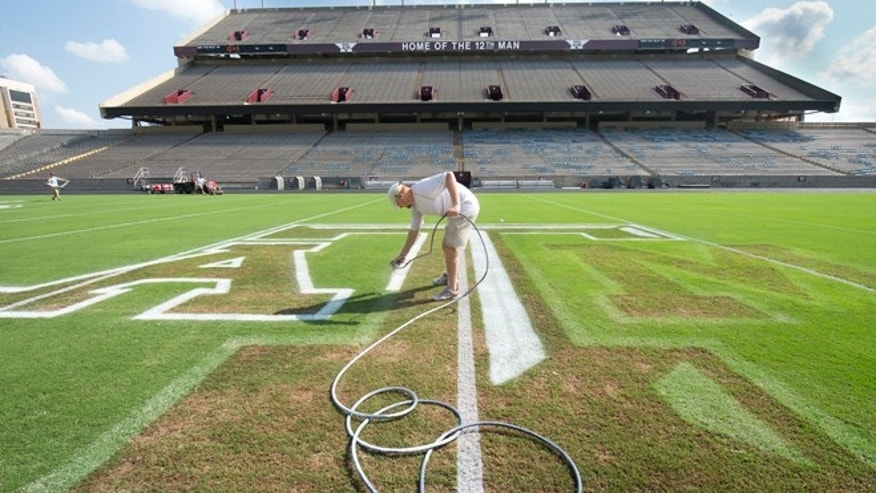Sept. 12, 2013: Jaxon Bailey paints the outline of the midfield logo at Kyle Field in College Station, Texas, in preparation for Saturday's NCAA college football game between Texas A&M and Alabama.  (AP/Bryan-College Station Eagle, Stuart Villanueva)