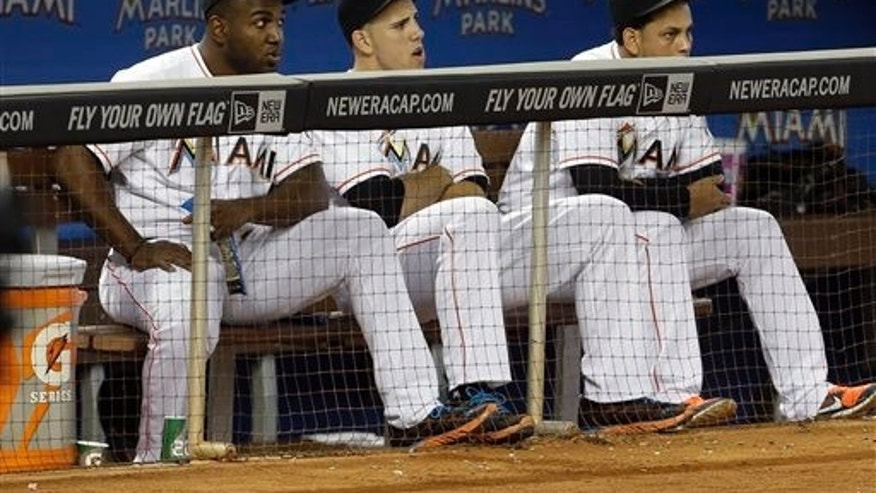 Miami Marlins starting pitcher Jose Fernandez, center, sits in the dugout with teammates Marcell Ozuna, left, during a baseball game against the Atlanta Braves, Thursday, Sept. 12, 2013, in Miami. Fernandez pitched his last game of the season Wednesday. (AP Photo/Lynne Sladky)