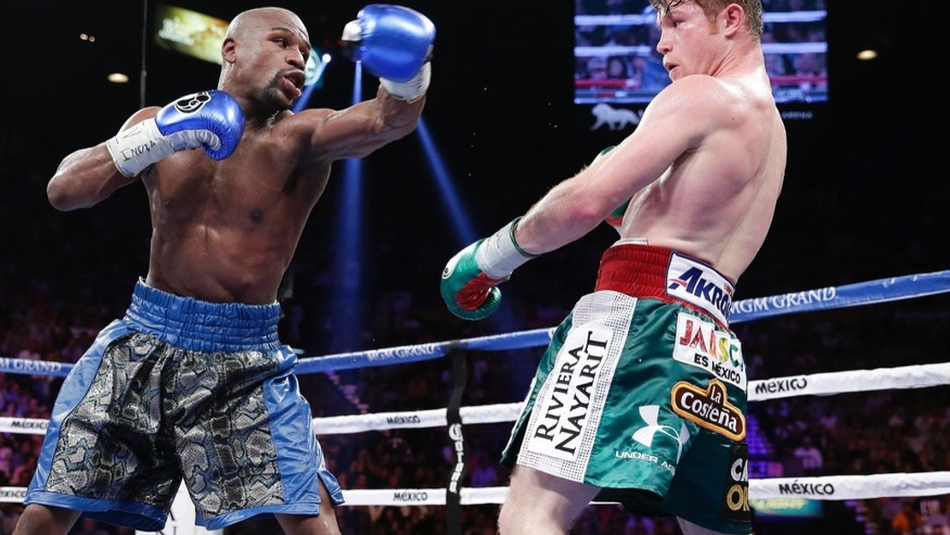 Floyd Mayweather Jr. throws a jab at Canelo Alvarez in the eighth round during a 152-pound title fight, Saturday, Sept. 14, 2013, in Las Vegas. (AP Photo/Eric Jamison)