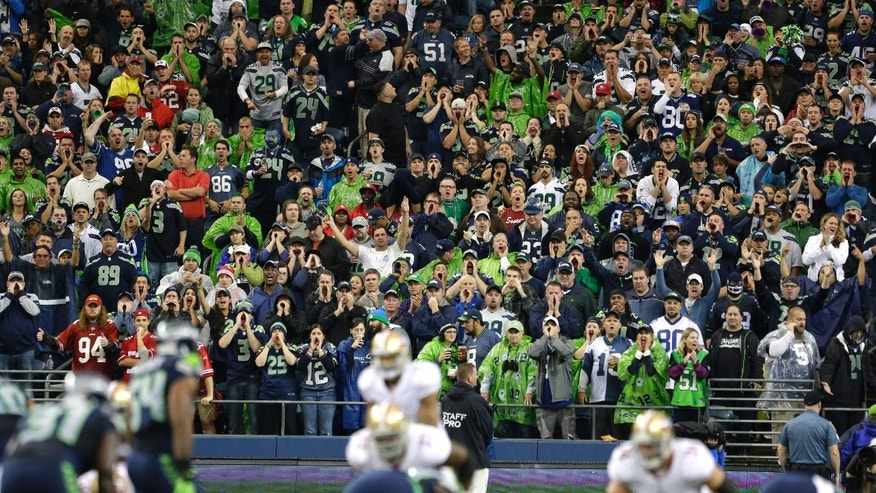 Seattle Seahawks fans yell during a San Francisco 49ers possession in the first half of an NFL football game, Sunday, Sept. 15, 2013, in Seattle.