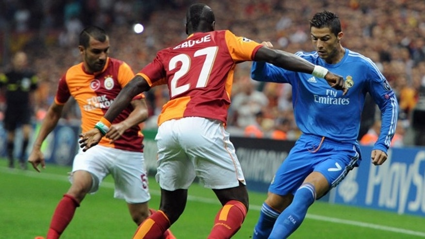 Emmanuel Eboue of Galatasaray, centre, vies for the ball with Real Madrid's Cristian Ronaldo, during their  Champions League Group B soccer match, in Istanbul, Turkey, Tuesday, Sept. 17, 2013. (AP Photo)