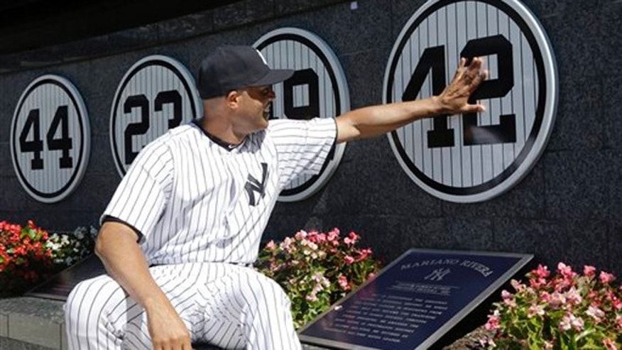 Mariano Rivera touches his plaque in Monument Park as he is honored in a pregame ceremony at Yankees Stadium, Sunday, Sept. 22, 2013, in New York.
