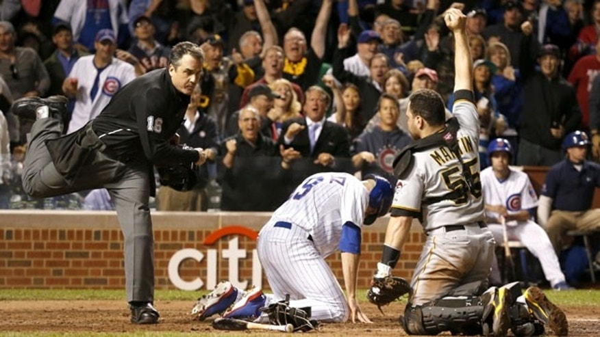 September 23, 2013: Home plate umpire Mike DiMuro calls Chicago Cubs' Nate Schierholtz out at home as Pittsburgh Pirates catcher Russell Martin shows DiMuro the ball during the ninth inning Monday in Chicago (AP Photo)