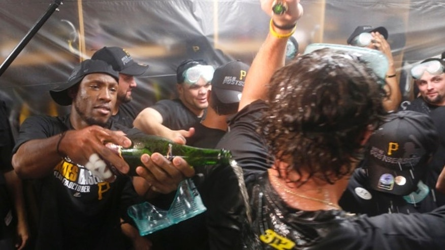Pittsburgh Pirates left fielder Starling Marte, left, celebrates with teammates  after the Pirates clinched a post season berth with a 2-1 win over the Chicago Cubs Monday, Sept. 23, 2013, in Chicago. (AP Photo/Charles Rex Arbogast)