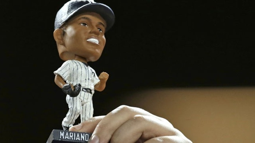 September 24, 2013: A fan holds up a Mariano Rivera bobblehead doll during the New York Yankees' baseball game against the Tampa Bay Rays Tuesday in New York. (AP Photo/Kathy Willens)