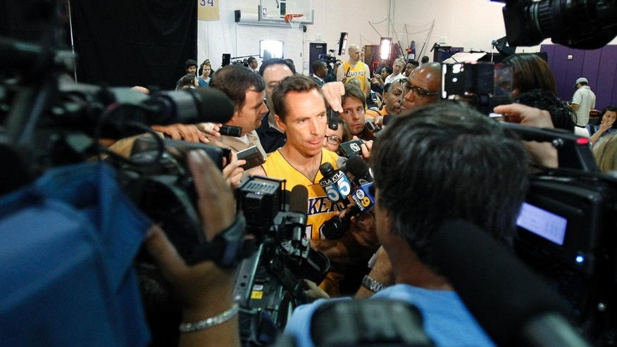 Los Angeles Lakers guard Steve Nash, center, talks to reporters during the NBA basketball team's media day Saturday, Sept. 28, 2013, in El Segundo, Calif. (AP Photo/Alex Gallardo)