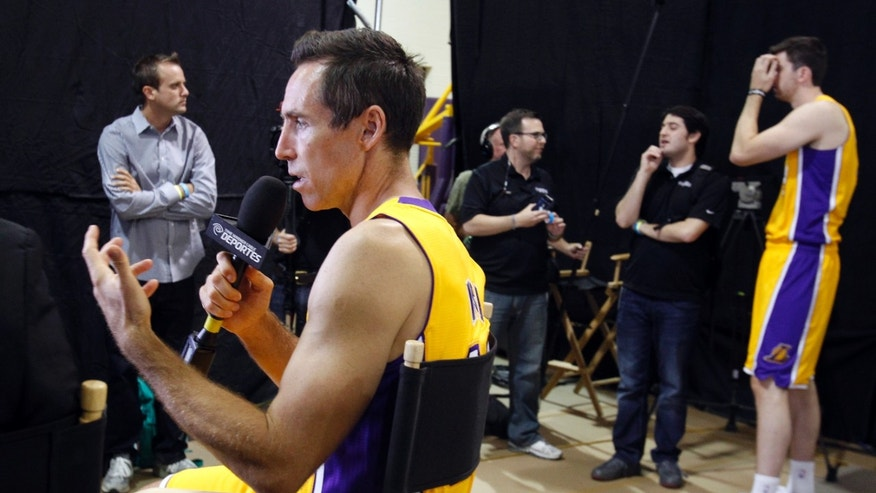 Los Angeles Lakers guard Steve Nash, left, talks with a reporter as forward Ryan Kelly, right, waits his turn to speak during the NBA basketball teams' media day Saturday, Sept. 28, 2013, in El Segundo, Calif. (AP Photo/Alex Gallardo)