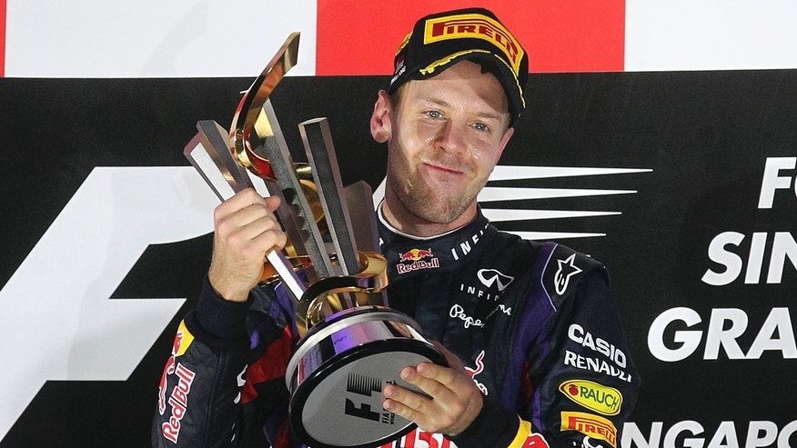 FILE - In this Sept. 22, 2013 file photo, Red Bull driver Sebastian Vettel of Germany celebrates on the podium after winning the Singapore Formula One Grand Prix on the Marina Bay City Circuit in Singapore. Formula One championship leader Vettel is cautious about the prospects of Red Bull continuing its dominance at this weekend's Korean Grand Prix, saying the layout of the circuit does not suit the car's strengths. The Korean Grand Prix is scheduled on Oct. 4, 2013. (AP Photo/Wong Maye-E, File)