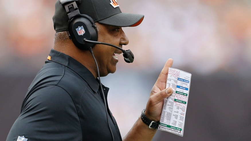 Cincinnati Bengals head coach Marvin Lewis talks on his headset in the first quarter of an NFL football game against the Cleveland Browns Sunday, Sept. 29, 2013, in Cleveland. (AP Photo/Tony Dejak)