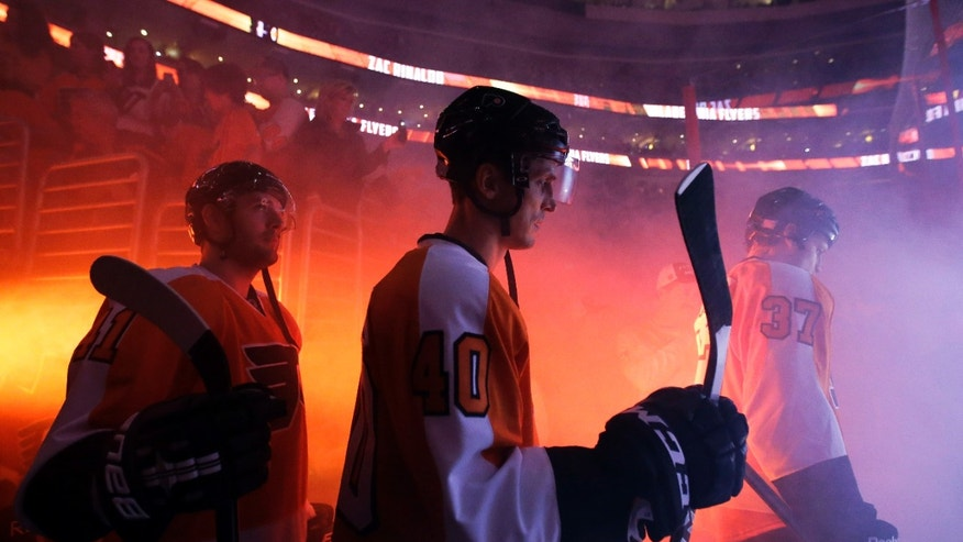Philadelphia Flyers' Vincent Lecavalier (40) waits for introductions with Andrej Meszaros (41), of Slovakia, and Jay Rosehill (37) before of an NHL hockey game against the Toronto Maple Leafs, Wednesday, Oct. 2, 2013, in Philadelphia. (AP Photo/Matt Slocum)