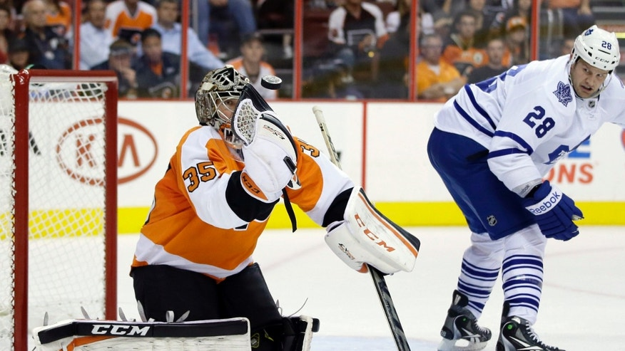 Philadelphia Flyers' Steve Mason, left, blocks a shot as Toronto Maple Leafs' Colton Orr looks on during the first period of an NHL hockey game on Wednesday, Oct. 2, 2013, in Philadelphia. (AP Photo/Matt Slocum)