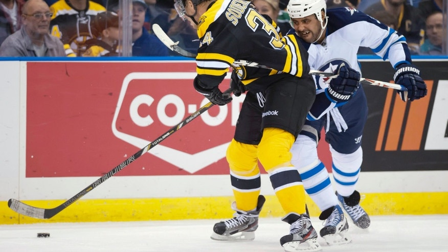 Boston Bruins forward Carl Soderberg, left, and Winnipeg Jets defenseman Dustin Byfuglien vie for the puck during the first period of an NHL hockey preseason game Friday, Sept. 27, 2013, in Saskatoon, Saskatchewan. (AP Photo/The Canadian Press, Liam Richards)