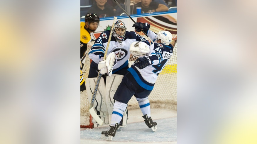 Boston Bruins forward Jarome Iginla watches as Winnipeg Jets forward Devin Setoguchi collides with goalie Al Montoya during the second period of an NHL hockey preseason game Friday, Sept. 27, 2013, in Saskatoon, Saskatchewan. (AP Photo/The Canadian Press, Liam Richards)