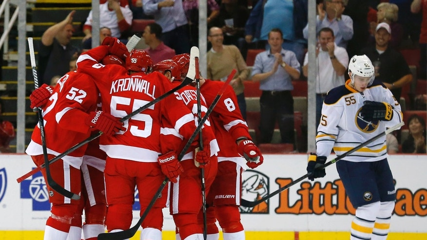 Detroit Red Wings center Pavel Datsyuk (13), of Russia, celebrates his goal with teammates against the Buffalo Sabres during the first period of an NHL hockey game in Detroit, Wednesday, Oct. 2, 2013. (AP Photo/Paul Sancya)