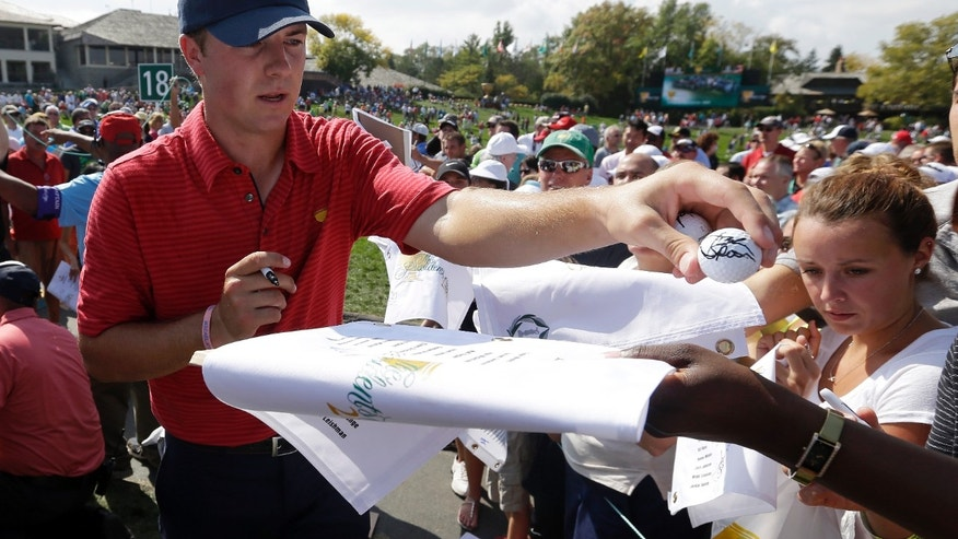 United States team player Jordan Spieth hands an autographed golf ball to a fan following a practice round for the Presidents Cup golf tournament at Muirfield Village Golf Club Wednesday, Oct. 2, 2013, in Dublin, Ohio. (AP Photo/Darron Cummings)