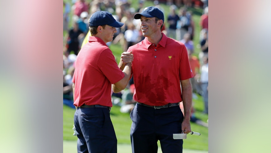 United States teammates Matt Kuchar, right, and Jordan Spieth shake hands following a practice round for the Presidents Cup golf tournament at Muirfield Village Golf Club Wednesday, Oct. 2, 2013, in Dublin, Ohio. (AP Photo/Darron Cummings)