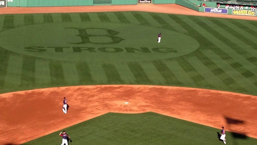 "A ""B Strong"" logo adorns the grass in centerfield at Fenway Park while the Boston Red Sox work out on Wednesday, Oct., 2, 2013, in Boston. The Red Sox will pay tribute to victims of the Boston Marathon bombings when the AL division series opens Friday. The logo matches the patch the team has worn since the April 15 explosions. (AP Photo/Jimmy Golen)"