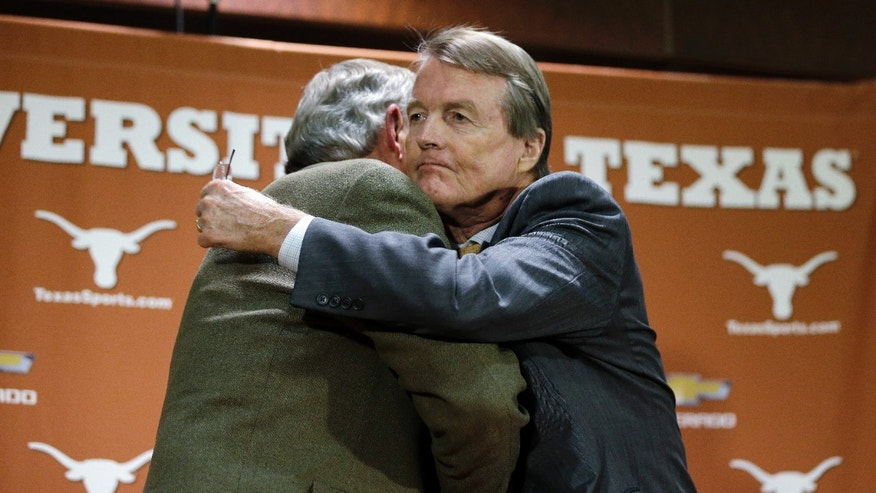 Texas athletic director DeLoss Dodds, left, is hugged by Texas president Bill Powers, right, following a news conference where Dodds formally announced his retirement, Tuesday,  Oct. 1, 2013, in Austin, Texas. Dodds, who has been with Texas for 32 years, will step down in August 2014. (AP Photo/Eric Gay)