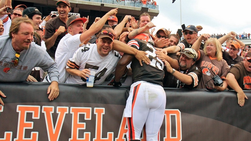 Cleveland Browns running back Chris Ogbonnaya (25) leaps into the Dawg Pound after a 1-yard touchdown catch against the Cincinnati Bengals in the fourth quarter of an NFL football game on Sunday, Sept. 29, 2013, in Cleveland. (AP Photo/Tony Dejak)