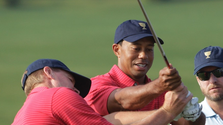 United States team player Tiger Woods, right, helps team player Steve Stricker with his swing before a team photo for the Presidents Cup golf tournament at Muirfield Village Golf Club Wednesday, Oct. 2, 2013, in Dublin, Ohio. (AP Photo/Jay LaPrete)