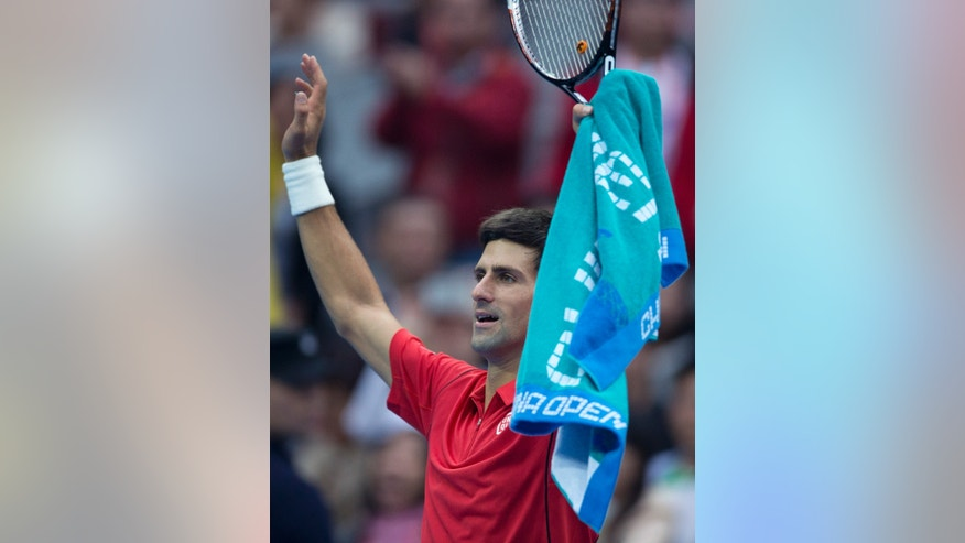 Novak Djokovic of Serbia acknowledges the spectators after defeating Fernando Verdasco of Spain during the China Open tennis tournament at the National Tennis Stadium in Beijing, China Thursday, Oct. 3, 2013.  (AP Photo/Andy Wong)