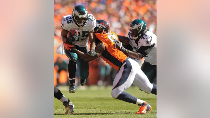 Philadelphia Eagles running back LeSean McCoy (25) takes a hit from Denver Broncos defensive end Robert Ayers (91) as Philadelphia Eagles tackle Jason Peters (71) tries to block in the first quarter of an NFL football game, Sunday, Sept. 29, 2013, in Denver. (AP Photo/Jack Dempsey)