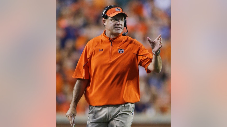 FILE - In this Sept. 7, 2013 file photo, Auburn head coach Gus Malzahn gestures in the first half of an NCAA college football game against Arkansas State in Auburn, Ala. Mississippi coach Hugh Freeze says he grabbed his phone on Sunday for one final text exchange with Auburn coach Malzahn. The gist of the conversation: It's hard playing against friends, so we'll talk when this is over. Mississippi plays Auburn Saturday, Oct. 5 at Auburn. (AP Photo/Dave Martin, Filoe)