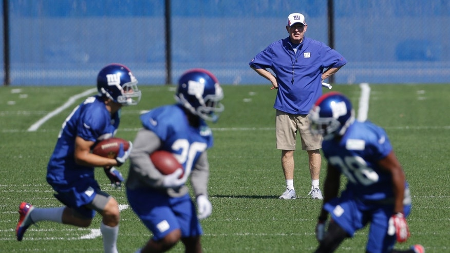 New York Giants head coach Tom Coughlin, top, watches as the defense works out during NFL football practice, Wednesday, Oct. 2, 2013, in East Rutherford, N.J. (AP Photo/Julio Cortez)