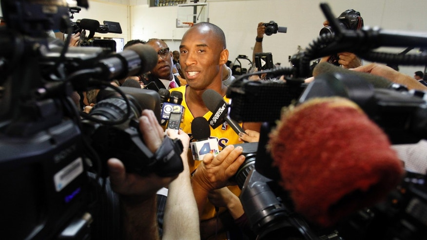 Los Angeles Lakers guard Kobe Bryant, center, talks to reporters during the NBA basketball team's media day Saturday, Sept. 28, 2013, in El Segundo, Calif. (AP Photo/Alex Gallardo)