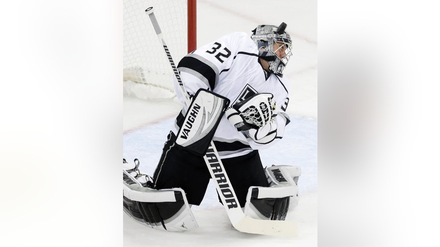 Los Angeles Kings goalie Jonathan Quick ducks as a shot misses his head during the first period of an NHL hockey game against the Minnesota Wild, Thursday, Oct. 3, 2013, in St. Paul, Minn. (AP Photo/Jim Mone)