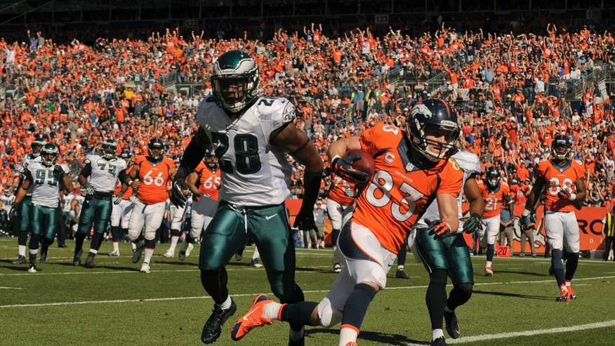 Denver Broncos wide receiver Wes Welker (83) crosses the goal line for a touchdown against Philadelphia Eagles strong safety Earl Wolff (28) in the first quarter of an NFL football game, Sunday, Sept. 29, 2013, in Denver. (AP Photo/Jack Dempsey)