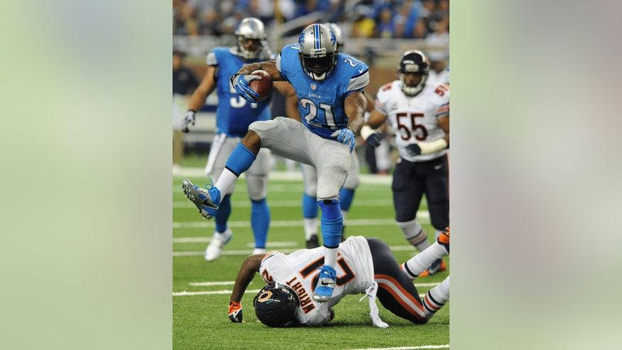 Detroit Lions running back Reggie Bush (21) jumps over Chicago Bears strong safety Major Wright (21) as he runs for a 37-yard touchdown during the second quarter of an NFL football game at Ford Field in Detroit, Sunday, Sept. 29, 2013. (AP Photo/Jose Juarez)