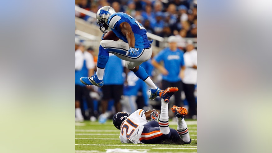 Detroit Lions running back Reggie Bush, top, jumps over Chicago Bears strong safety Major Wright (21) while heading for the end zone on a 37-yard touchdown run during the second quarter of an NFL football game at Ford Field in Detroit, Sunday, Sept. 29, 2013. (AP Photo/Paul Sancya)