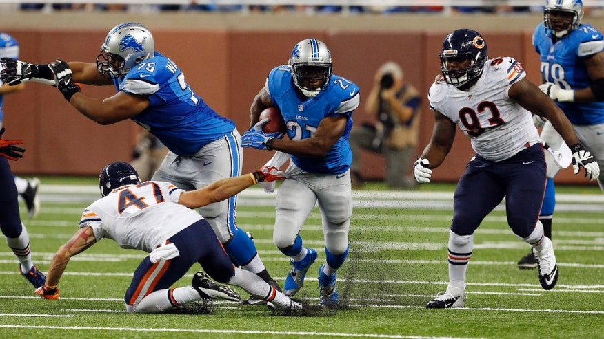 Detroit Lions running back Reggie Bush (21) breaks through the Chicago Bears defense during the first quarter of an NFL football game at Ford Field in Detroit, Sunday, Sept. 29, 2013. Bush rushed for 139 yards in the Lions' 40-32 win. (AP Photo/Paul Sancya)