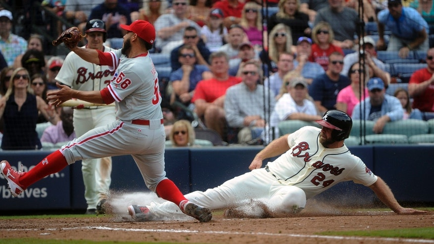 Atlanta Braves' Evan Gattis, right, scores on a wild pitch as Philadelphia Phillies pitcher Cesar Jimenez (56) covers home plate during the sixth inning of a baseball game on Sunday, Sept. 29, 2013, in Atlanta. (AP Photo/John Amis),