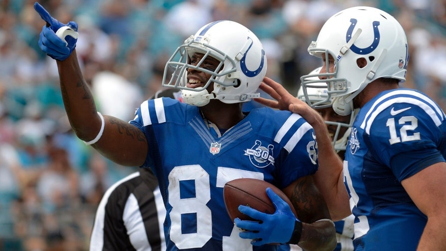 ADVANCE FOR WEEKEND EDITIONS, OCT. 5-6 - FILE - In this Setp. 29, 2013, file photo, Indianapolis Colts wide receiver Reggie Wayne (87) celebrates with quarterback Andrew Luck (12) after catching a touchdown pass in the second half of an NFL football game against the Jacksonville Jaguars in Jacksonville, Fla. Wayne is on the verge of joining the 1,000-catch club, and it could happen this Sunday against the Seatte Seahawks. (AP Photo/Phelan M. Ebenhack, File)