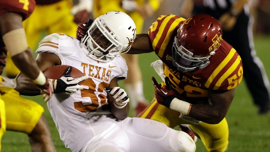 Texas running back Johnathan Gray is tackled by Iowa State linebacker Jeremiah George, right, during the second half of an NCAA college football game on Thursday, Oct. 3, 2013, in Ames, Iowa.  Texas won 31-30. (AP Photo/Charlie Neibergall)