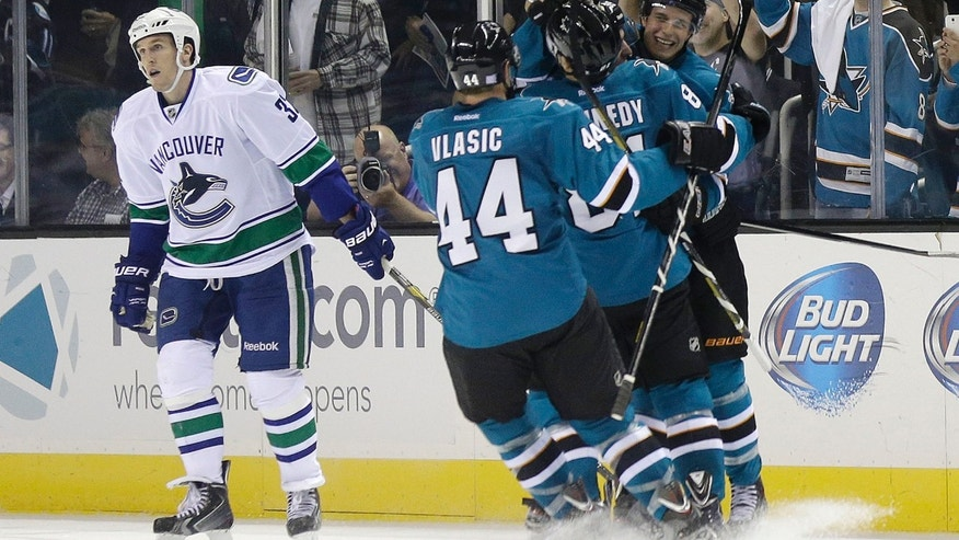San Jose Sharks goalie Antti Niemi, of Finland, stops a shot by the Vancouver Canucks during the second period of an NHL hockey game Thursday, Oct. 3, 2013, in San Jose, Calif. (AP Photo/Marcio Jose Sanchez)