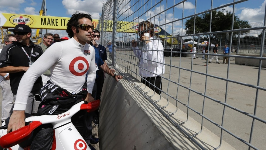 Dario Franchitti, of Scottland, watches as a temporary chicane is installed in turn one before practice for the IndyCar Grand Prix of Houston auto race, Friday, Oct. 4, 2013, in Houston. Practice was delayed due to surface issues in turn one. (AP Photo/David J. Phillip)